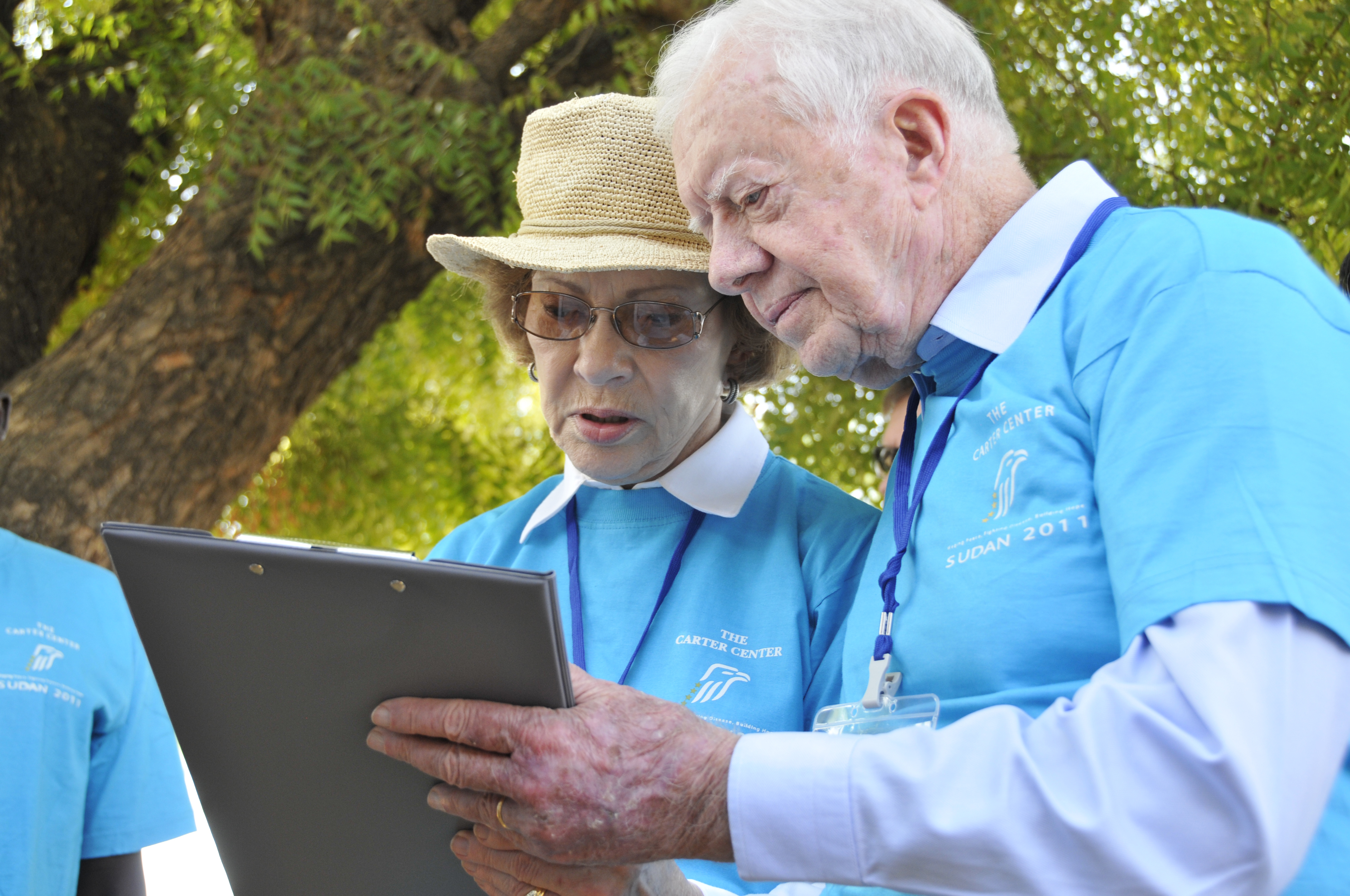 A white woman (Rosalynn Carter) in a white collared shirt with a blue t-shirt over it and a tan rimmed hat looks at a clipboard held by a white man (Jimmy Carter) in a white collared shirt with a blue t-shirt over it.
