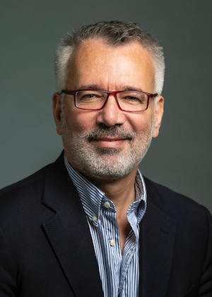Headshot of a man with short grey hair and a grey beard wearing maroon glasses, a blue button up shirt without a tie, and a black suit jacket.