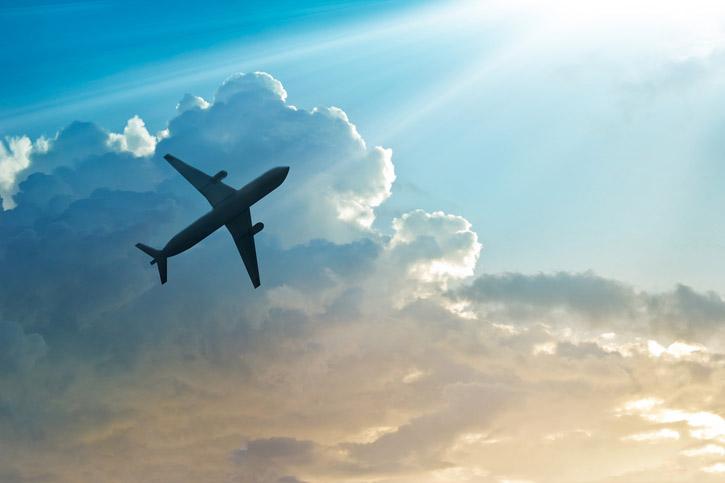 An airplane flies through partly cloudy skies