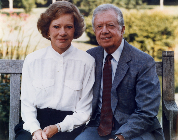 A woman in a white, long-sleeve shirt and a man in a blue suit and tie sit side-by-side on a bench and look at the camera.