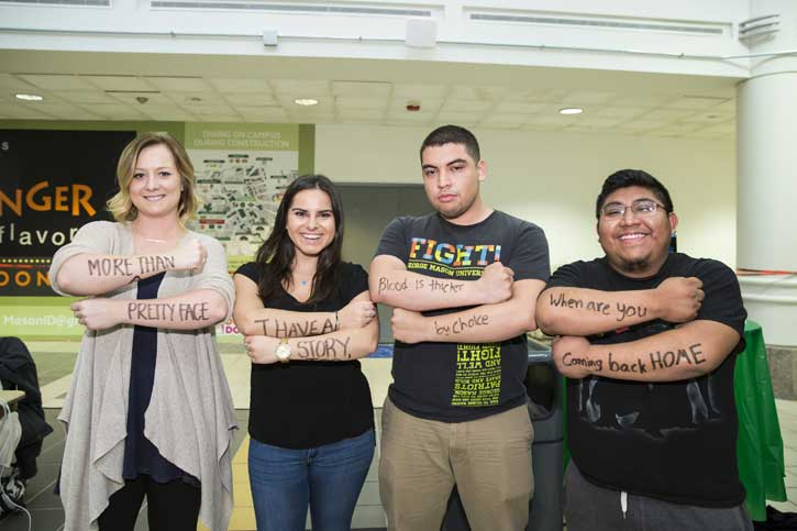 Students who participated in the Dear World storytelling project display phrases on their forearms that tell their stories.