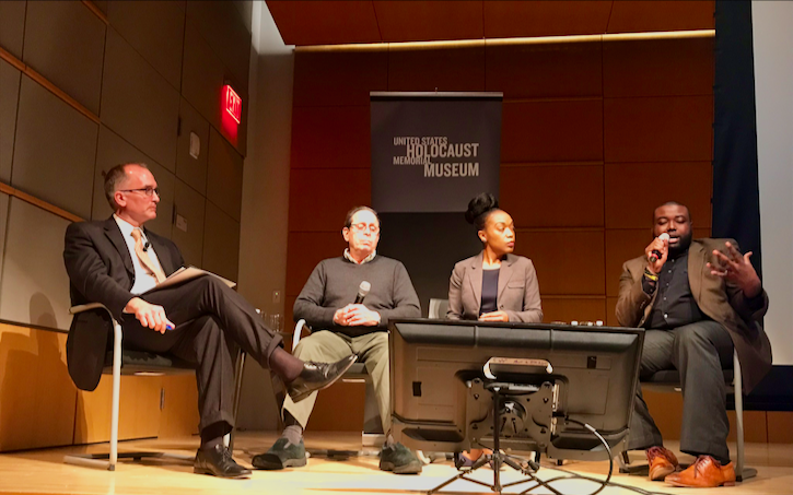 ID: Four people seated on a stage in a panel formation. On the right an African American man is holding a microphone and speaking.