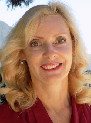 Photo of Karina Korostelina, a white woman with light blonde hair. She is smiling and is wearing earrings and a red shirt.