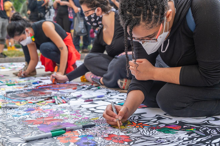 A number of people wearing facemarks sit on the ground outside and color in white banners with designs on them to reflect solidarity with the Black Lives Matter movement.