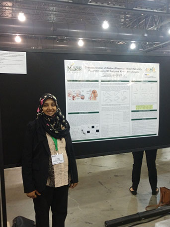 Graduate student Khadija Zaidi-Rashid stands in front of a poster board with her research in a big fluorescent-lit room.