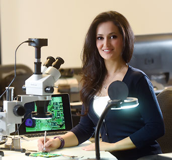 Graduate student Sahar Mazloom sits at a desk with a miscroscope, computer and other equipment