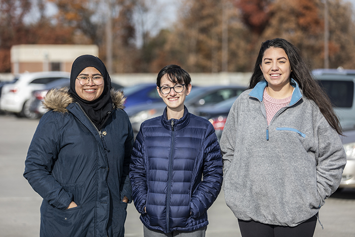 research team poses in front of parked cars