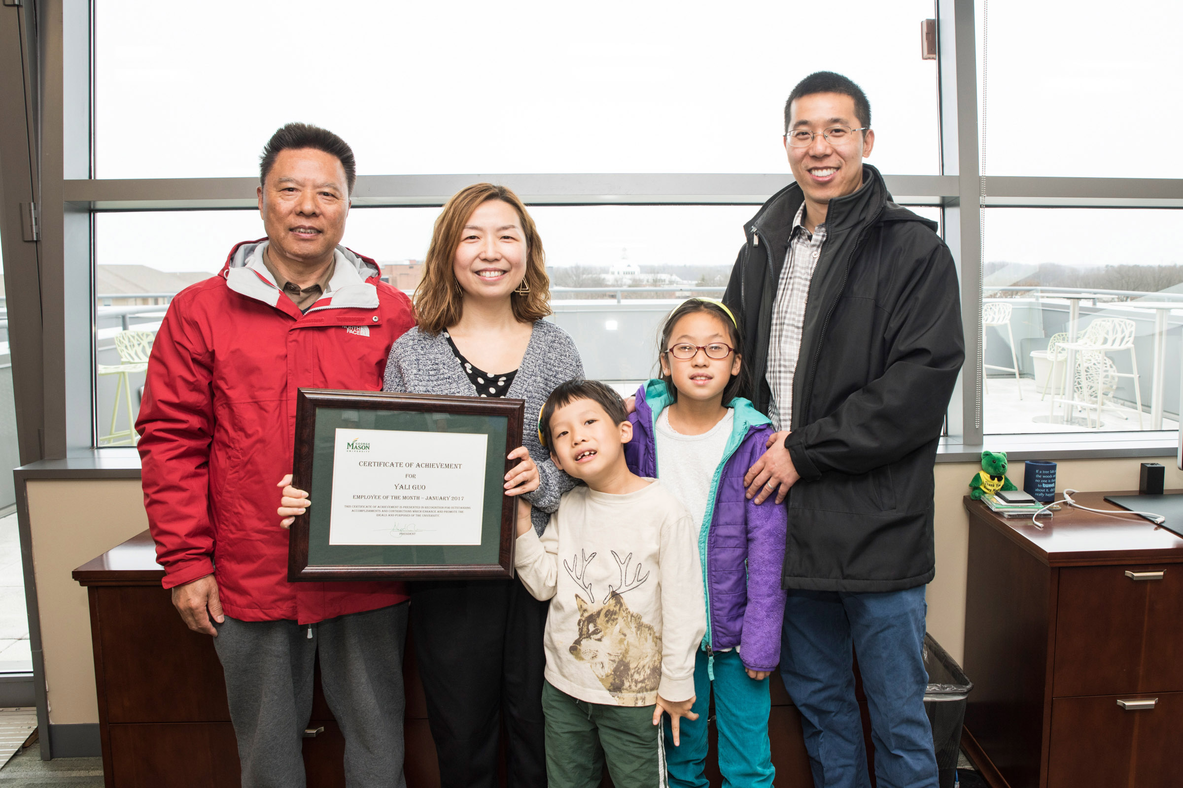 Yali Guo and her family pose with her Employee of the Month award
