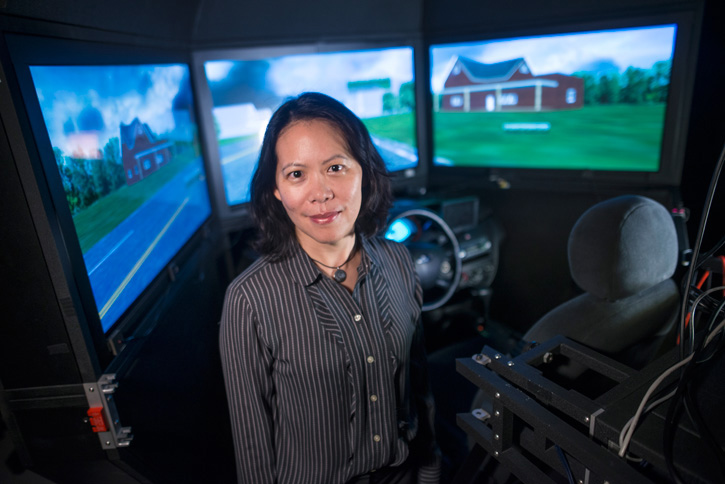 Yi-Ching Lee stands next to a driver simulator where she conducts her research