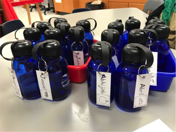 Water bottles with students' names are clustered on a table at the school.